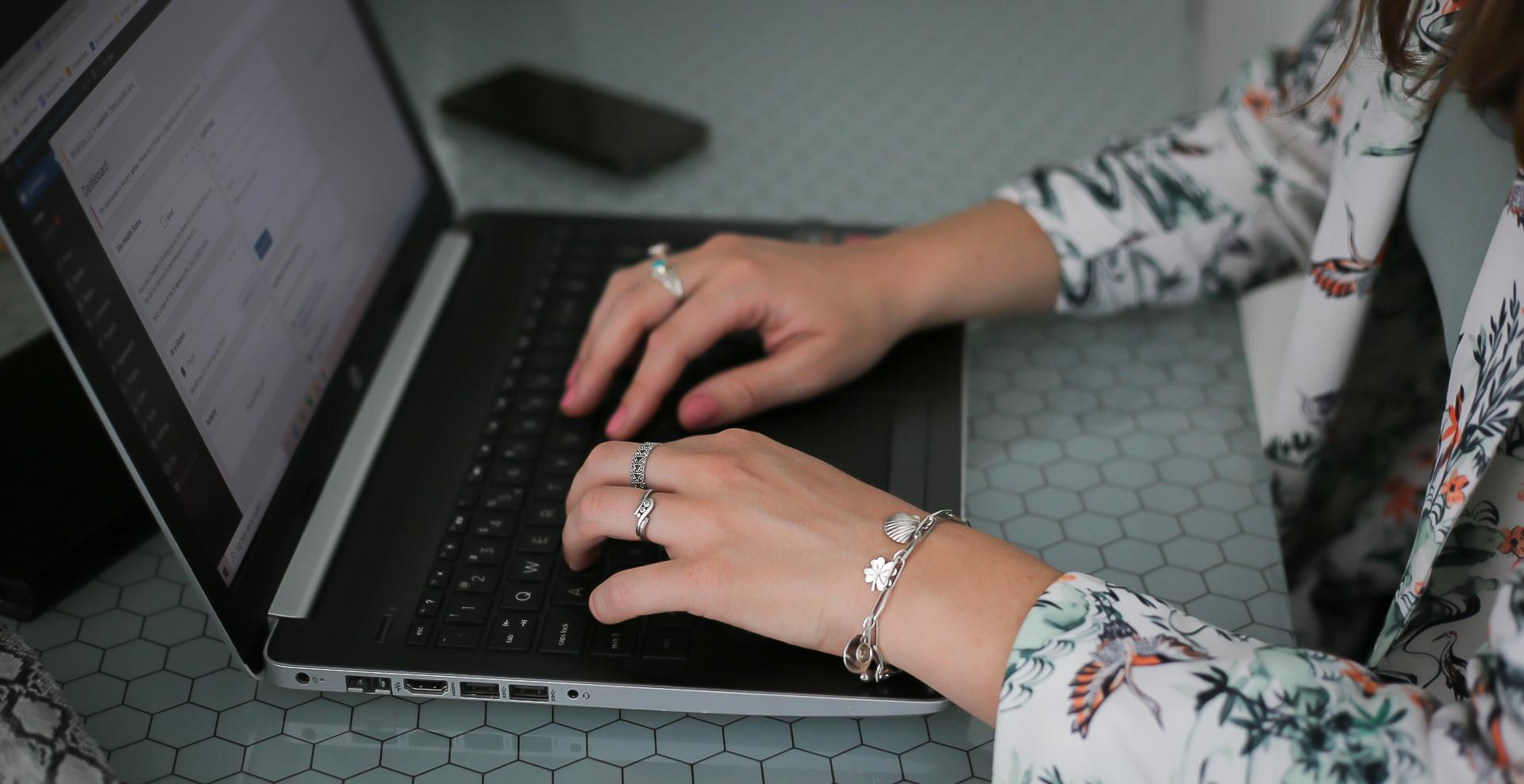 Handen op toetsenbord, werkend aan WordPress website